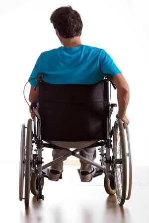 Foto de Rear view of handicapped man in wheelchair - Imagen libre de derechos