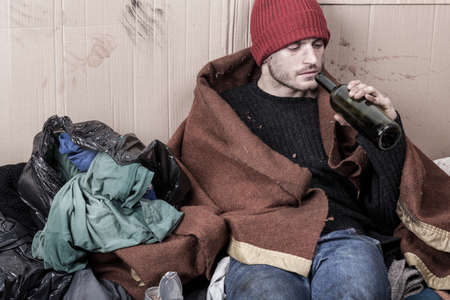 Foto de Homeless drinking cheap wine on the street - Imagen libre de derechos