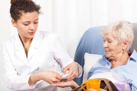 Foto de Home nurse giving elderly woman vitamin pills - Imagen libre de derechos