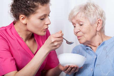 Foto de The professional nurse feeding an older lady - Imagen libre de derechos