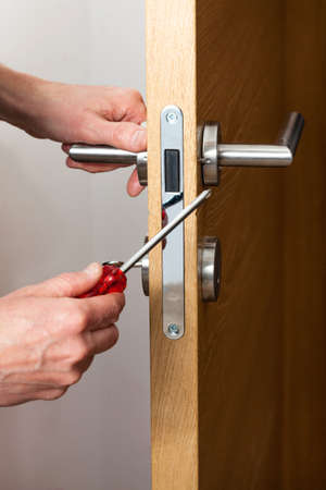 Foto de Hands repairing a door lock with a screwdriver - Imagen libre de derechos