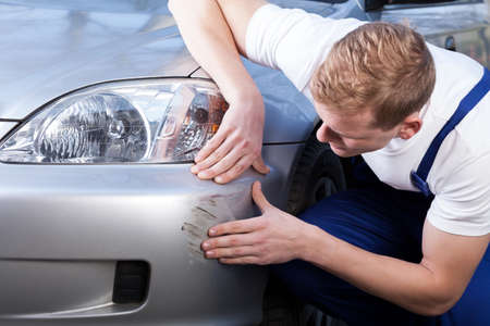 Photo for A man trying to fix a scratch on a car body - Royalty Free Image