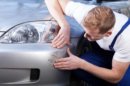 Foto de A man trying to fix a scratch on a car body - Imagen libre de derechos