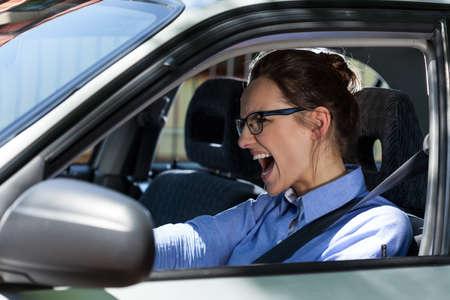 Foto de Young elegant woman stopping the car and screaming  - Imagen libre de derechos