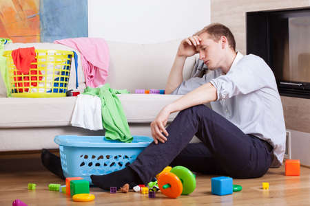 Photo pour Lonly tired father sitting with child's toys - image libre de droit