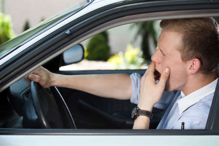 Photo pour Bored man in car waiting in traffic jam - image libre de droit
