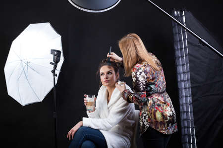 Photo for Side view of a make-up artist preparing female model for photo shoot - Royalty Free Image