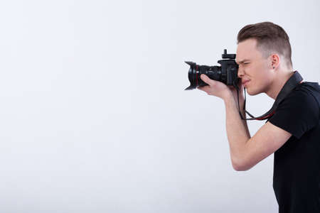Photo for Side view of a young photographer on isolated white background - Royalty Free Image