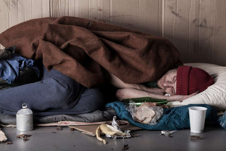 Foto de Horizontal view of a poor man sleeping on the street - Imagen libre de derechos