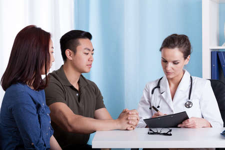 Photo for Asian couple during visit at doctor's office, horizontal - Royalty Free Image