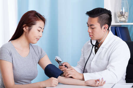 Foto de Asian male doctor taking blood pressure of a female patient - Imagen libre de derechos