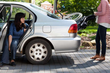 Photo pour Girl taking wheelchair from car to provide mobility for disabled woman - image libre de droit
