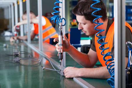 Photo pour Men during precision work on production line, horizontal - image libre de droit