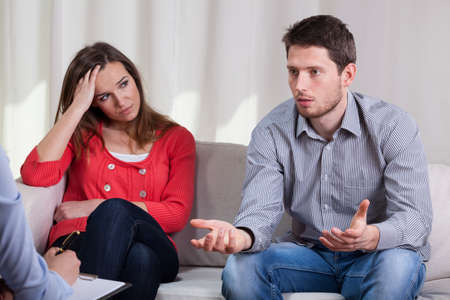 Foto de Young marriage in crisis trying solve problem during psychotherapy  - Imagen libre de derechos