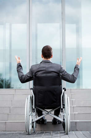 Foto de Back view of a disabled man in front of stairs, vertical - Imagen libre de derechos