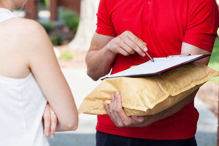 Photo pour Close-up of a delivery man asking for a signature - image libre de droit