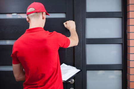 Photo pour Back view of a delivery man knocking on the client's door - image libre de droit