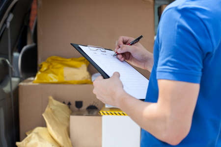 Photo pour Close-up of a courier's hand writing on clipboard - image libre de droit