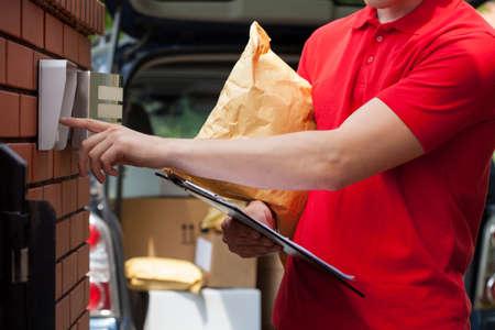 Photo pour Close-up of a courier with packages dialing intercom - image libre de droit