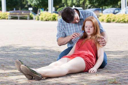 Foto de Inappropriate giving water after the fainting, horizontal - Imagen libre de derechos