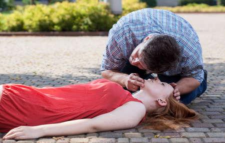 Foto de View of man checking if woman's conscious - Imagen libre de derechos