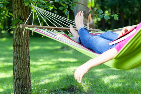 Foto de Young lady resting on hammock with book summer - Imagen libre de derechos