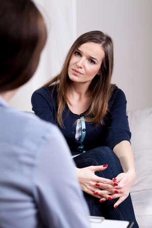 Foto de Sad depressed young woman on psychotherapy session  - Imagen libre de derechos