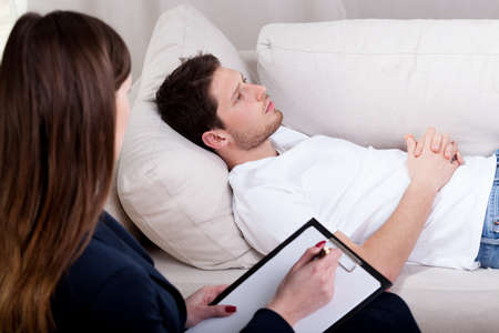 Photo pour Young therapist working with patient on hypnosis - image libre de droit