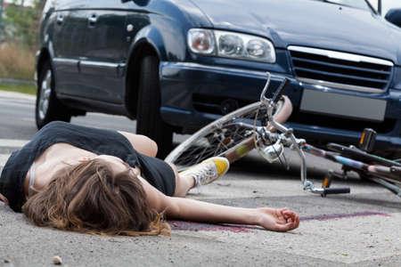 Foto de Unconscious female cyclist lying on street after road accident - Imagen libre de derechos
