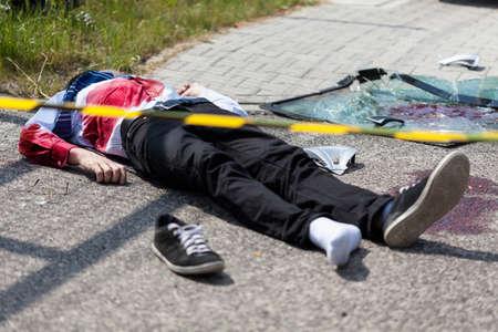 Foto de Caution tape and dead man lying on the street, horizontal - Imagen libre de derechos