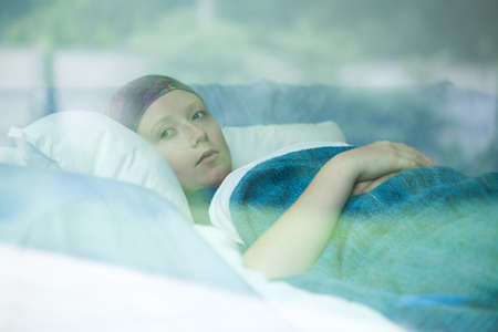 Photo pour Young woman in bed suffering from cancer - image libre de droit