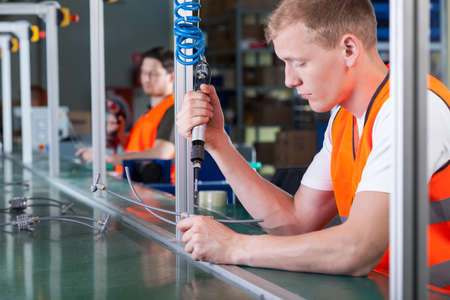 Photo for Concentrated young workers on production line, horizontal - Royalty Free Image