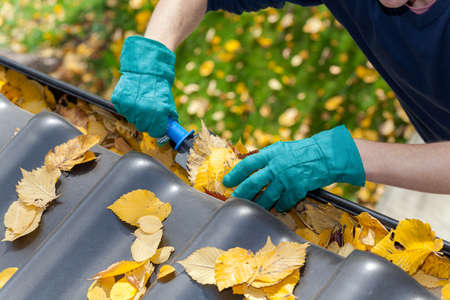 Photo pour A man taking autumn leaves out of gutters - image libre de droit