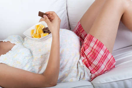 Pregnant woman eating chocolate in the morning