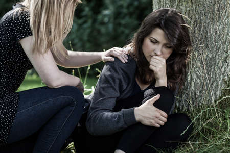 Photo pour Young woman comforting her mourning friend - image libre de droit