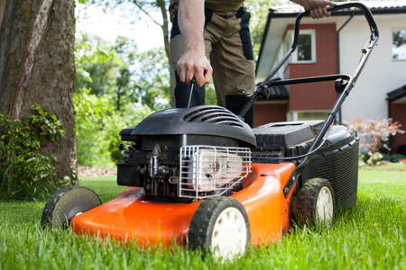 Foto de Turning on the lawn mower by gardener - Imagen libre de derechos