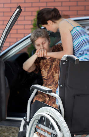 Photo pour Girl helping disabled senior woman coming out of car - image libre de droit