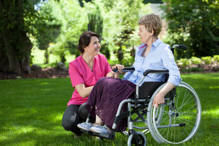 Foto de Happy senior woman on wheelchair with caring caregiver outdoors - Imagen libre de derechos