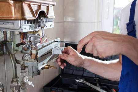 Photo pour Repairman fixing a gas water heater with a screwdriver - image libre de droit