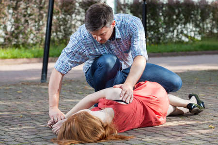 Photo for Man lying unconscious girl in recovery position - Royalty Free Image