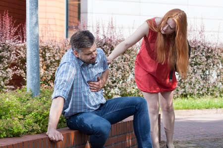 Foto de Young woman want to help man with chest pain - Imagen libre de derechos