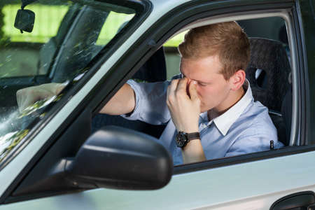 Photo pour View of tired businessman driving a car - image libre de droit