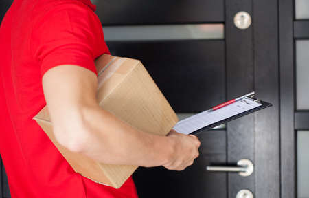 Photo pour Delivery guy waiting at front door with a parcel - image libre de droit