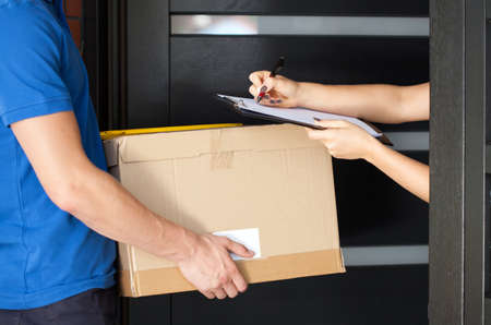 Foto de Delivery guy holding package while woman is signing documents - Imagen libre de derechos