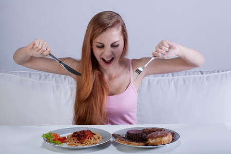 Photo pour Young girl eating a lot of food at once - image libre de droit