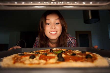 Photo pour Happy girl putting pizza into oven, horizontal - image libre de droit