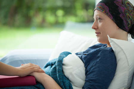 Photo pour Cancer woman lying in bed supported by mum - image libre de droit