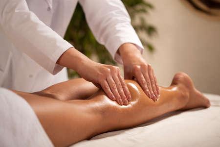 Photo pour Horizontal view of masseur massaging female calf - image libre de droit