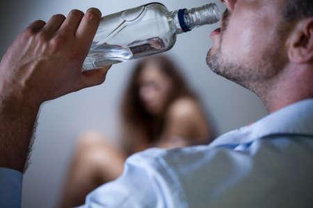 Foto de Drunk men with bottle and his frightened wife - Imagen libre de derechos