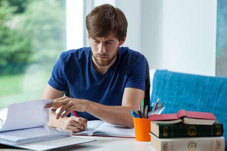 Foto de Young student learning and spending time behind the desk - Imagen libre de derechos